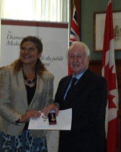Baron Denis Hoban receiving his Medal from his member of Parliament Laura Albanese M,P,P,  at the Lt Governor of Ontario committee Room , Queens Park, Parliament Buildings Toronto.