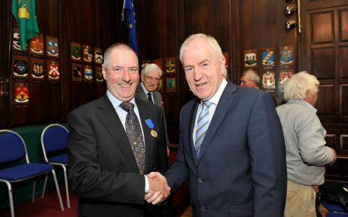 Minister Deenihan congratulates Cathaoir Ó Tighearnaigh on receiving his CIOM