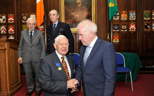 Minister Deenihan congratulates Ambassador Brian Ó Ceallaigh on receiving his CIOM