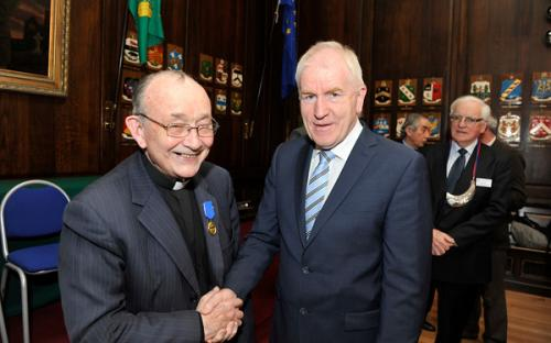 Minister Deenihan congratulates Monsignor Ó Fionnachta on receiving his CIOM